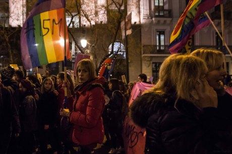 Mujer trans en la manifestación llevánuna una bandera arcoiris con el #15M (8.03.2018)